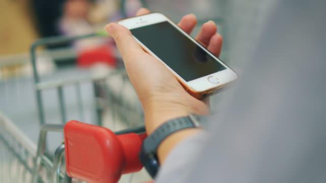 Vrouw met behulp van smartphone in de supermarkt
