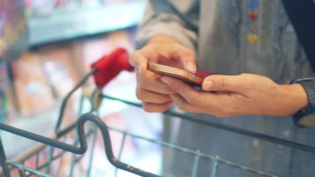 vídeos de stock, filmes e b-roll de mulher usando smartphone no supermercado - etiqueta mensagem