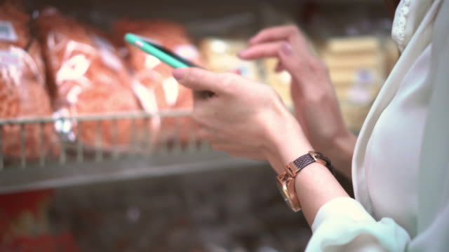 Woman using smartphone in supermarket,Close-up