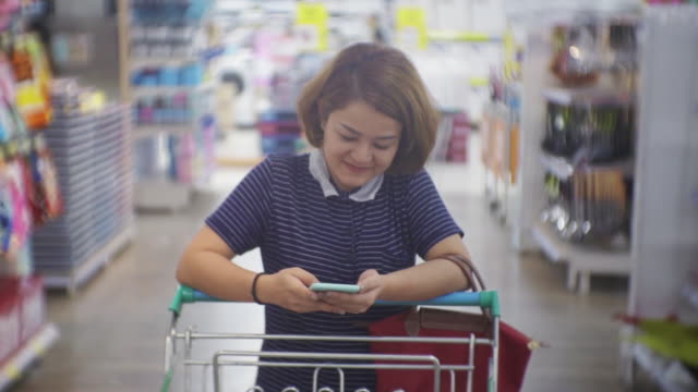 vídeos de stock e filmes b-roll de woman using smartphone in supermarket,slow motion - trabalhadora de colarinho branco