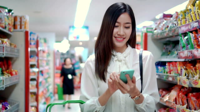 woman using smartphone in supermarket,slow motion - customer stock videos & royalty-free footage