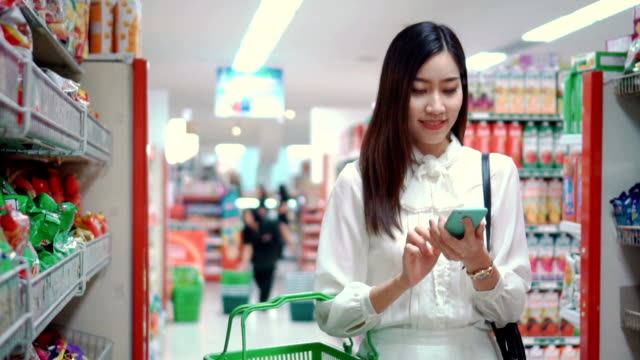 stockvideo's en b-roll-footage met vrouw met behulp van smartphone in de supermarkt, slow motion - shelf