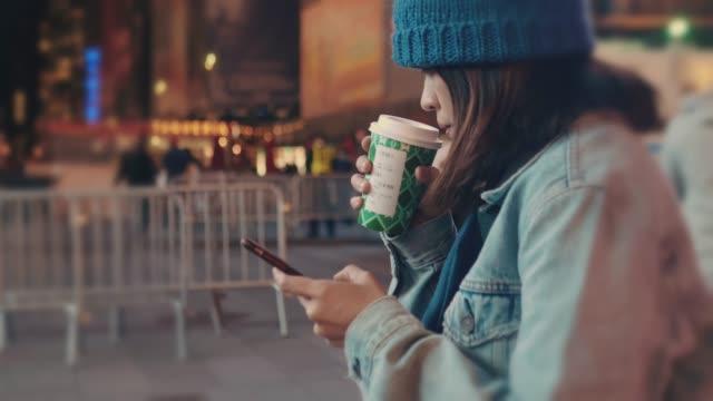 市ニューヨーク ニューヨークでスマート フォンを使用しての女性。 - ウィンターコート点の映像素材/bロール