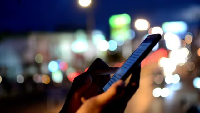 Woman using smartphone, night.