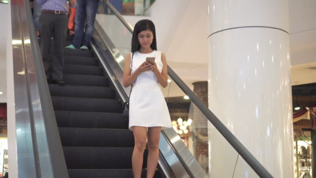 Woman using smartphone on escalator in shopping mall