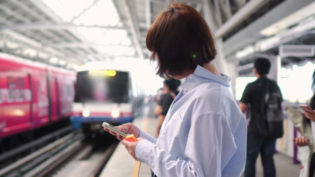 Woman using smartphone on on train station