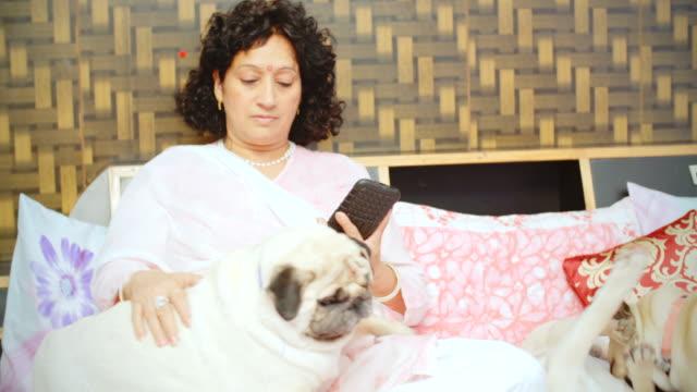 Frau mit Smartphone sitzen auf dem Bett mit ihren Hunden.
