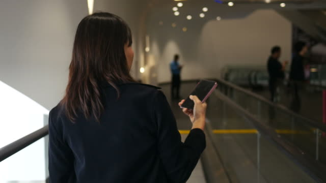 woman using smartphone while walking on corridor