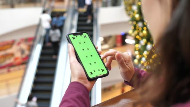 Frau mit Smartphone mit Greenscreen im Einkaufszentrum