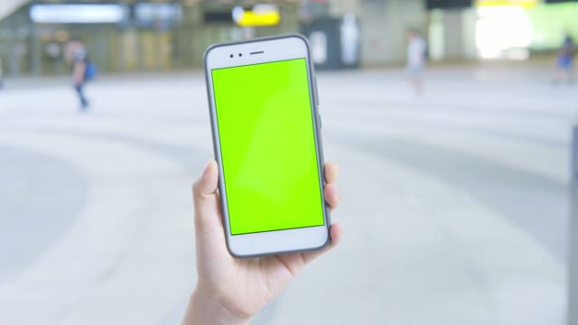 woman using smartphone with green screen on the street - portability video stock e b–roll