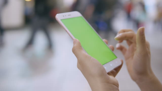 woman using smartphone with green screen on the street. - mobilità video stock e b–roll