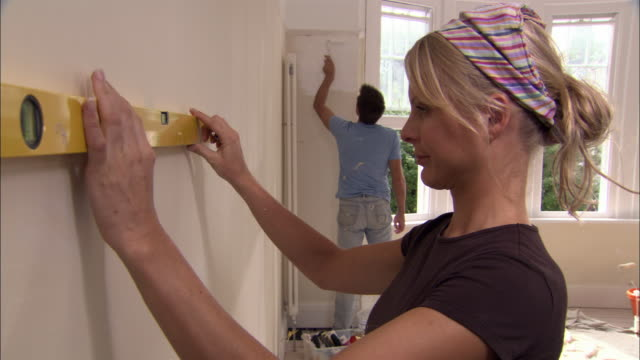 Woman using spirit level to draw line on wall while man paints wall in background