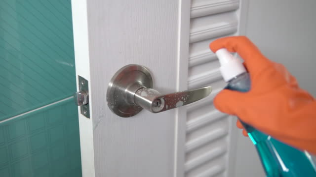 woman using spray alcohol for cleaning doorknob. - rubbing alcohol stock videos & royalty-free footage