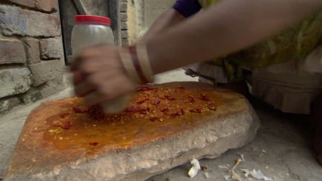 cu tu woman using stone to grind peppers and spices, agra, uttar pradesh, india - macinare video stock e b–roll