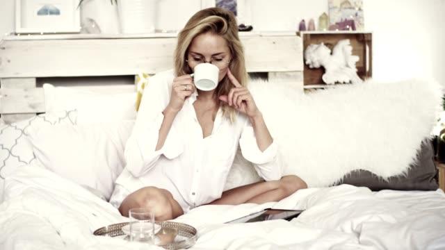 kvinna med surfplatta och dricka morgonkaffe i sängen - pyjamas bildbanksvideor och videomaterial från bakom kulisserna
