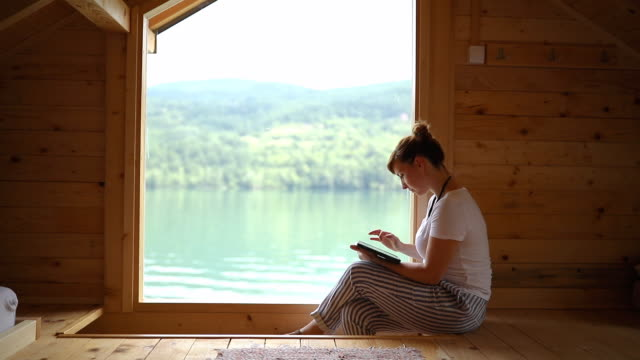 woman using tablet and enjoying in wooden house on lake - log cabin stock videos & royalty-free footage