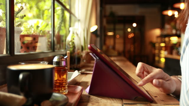 Woman using tablet at cafe