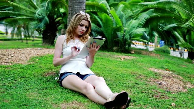 frau mit tablet im park - vakuum stock-videos und b-roll-filmmaterial