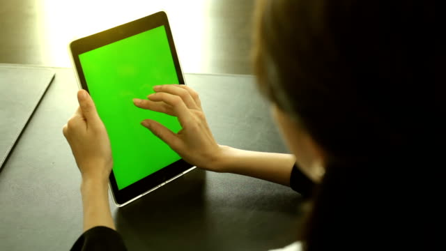 Woman Using Tablet at the table in offic. Green Screen