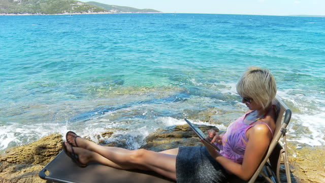 vídeos de stock, filmes e b-roll de hd dolly: mulher usando tablet ao mar - espreguiçadeira