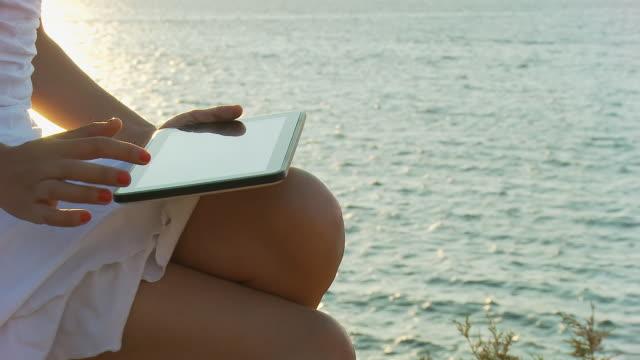 vídeos de stock e filmes b-roll de grou de hd: mulher usando tablet ao mar - vestido branco