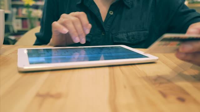 stockvideo's en b-roll-footage met vrouw met behulp van tablet pc voor online bankieren. - boekwinkel