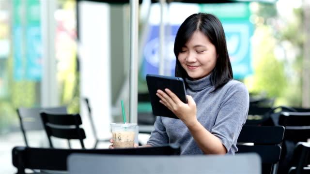 stockvideo's en b-roll-footage met vrouw met behulp van tablet pc in een koffieshop - artikel