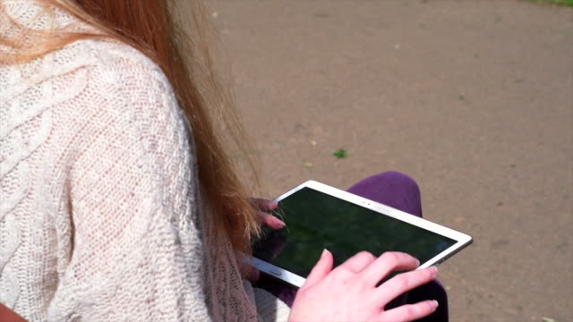 Woman Using Tablet In Park