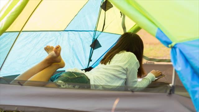 Donna che usa Compressa In campeggio