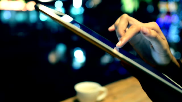 Woman Using Tablet PC and Drinking Coffee in Cafe.