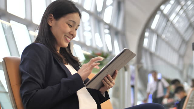 Woman using tablet PC at airport