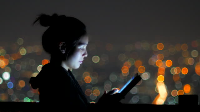 Woman using tablet pc at night with bokeh background