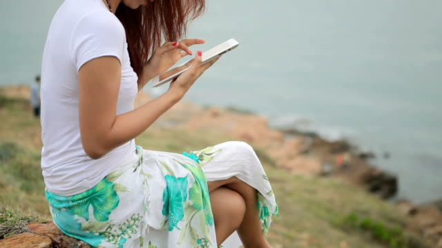 Woman using tablet pc on mountain