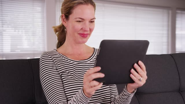 woman using tablet to video chat in living room, seated by windows during day - touchpad stock videos & royalty-free footage