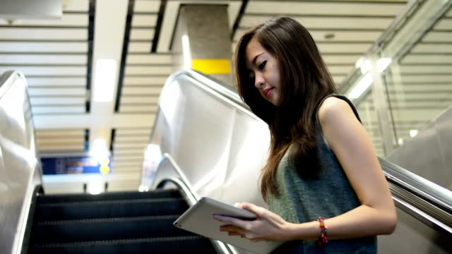 Woman using tablet while moving up on escalator