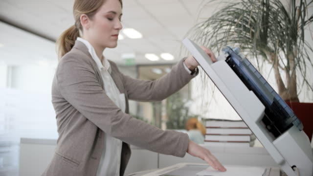 Woman using the copying machine in the office