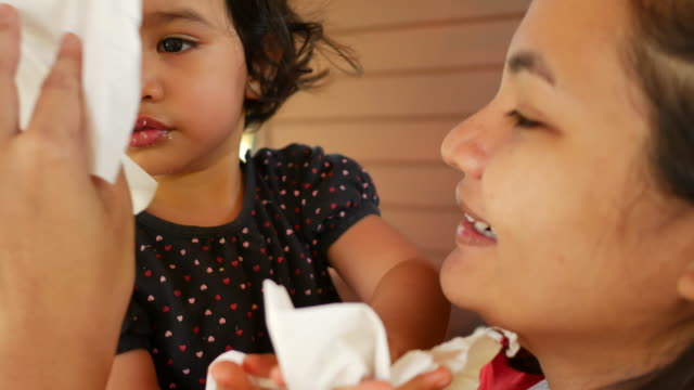 woman using tissue paper to clean granddaughter's mouth - tissue paper stock videos & royalty-free footage