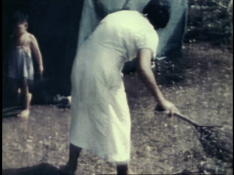 woman using twig broom to sweep campsite / guam - pacific war stock videos & royalty-free footage