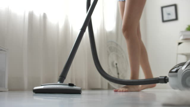 woman using vacuum cleaning on flooring at home - vacuum cleaner stock videos & royalty-free footage