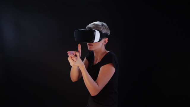 woman using virtual reality glasses. aiming with imaginary weapon - sparare video stock e b–roll