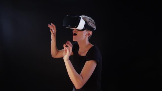 vidéos et rushes de femme à l'aide de lunettes de réalité virtuelle. explorer le monde virtuel - toucher et choisir les éléments - touche de couleur