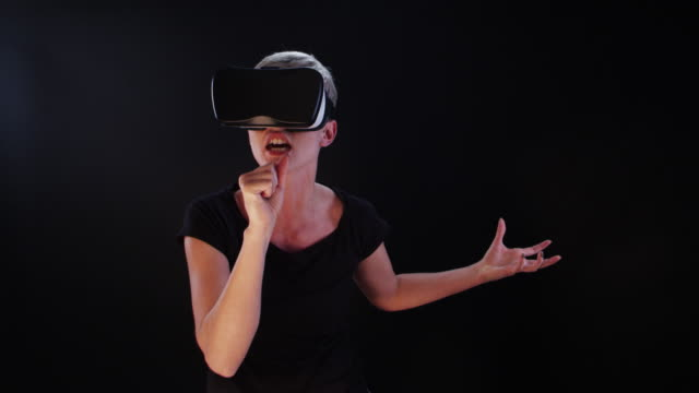 Woman using virtual reality glasses. Singing to a virtual microphone