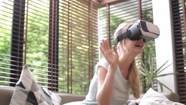 vidéos et rushes de femme avec vr lunettes à la maison - curiosité