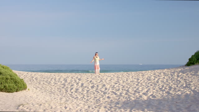 woman using VR glasses outside on a beach - shot-2: wide / appearing behind the hill