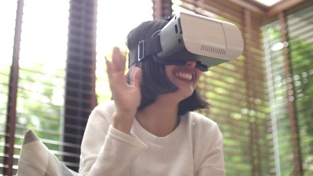 frau mit vr-headset zu hause - nur junge frauen stock-videos und b-roll-filmmaterial
