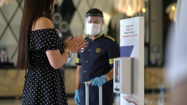 frau mit waschen hand desanitizer gel spender automat. - hotel stock-videos und b-roll-filmmaterial