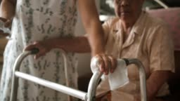 COVID-19 : Woman using wet wipe and alcohol cleaning mobility walker