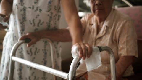 covid-19 : kvinna som använder våtservett och alkoholrengöring rörlighet walker - kroppsvård bildbanksvideor och videomaterial från bakom kulisserna