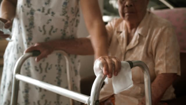 covid-19 : woman using wet wipe and alcohol cleaning mobility walker - prendersi cura del corpo video stock e b–roll