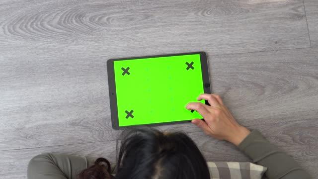 vídeos y material grabado en eventos de stock de mujer blanco tablet pc con pantalla verde en el piso - table top view